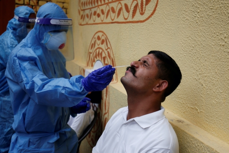 A healthcare worker wearing personal protective equipment takes a swab from a police officer for a rapid antigen test at a special testing centre for Gujarat police, amid the coronavirus outbreak, in Ahmedabad, India [File: Amit Dave/Reuters]