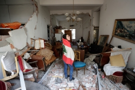 Farah Mahmoud, wrapped in a Lebanese flag, checks her parents' destroyed apartment.  Estimates say 6,200 buildings were damaged. [Hassan Ammar/AP Photo]