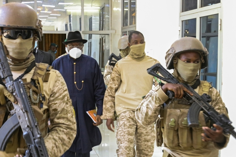 Former Nigerian President Goodluck Jonathan (left) walks alongside Colonel Assimi Goita behind two soldiers [H.Diakite/EPA-EFE/EPA]
