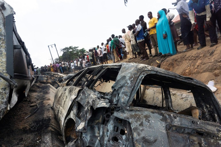 Bystanders look on at the wreckage of the truck in Lokoja [Haruna Yahaya/AFP]