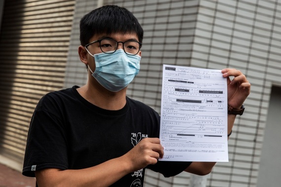 Joshua Wong speaks to the media while holding up a bail document after leaving Central Police Station in Hong Kong on September 24, 2020, after being arrested for unlawful assembly related to a 2019 protest against a government ban on face masks (Photo by ISAAC LAWRENCE / AFP) (AFP)