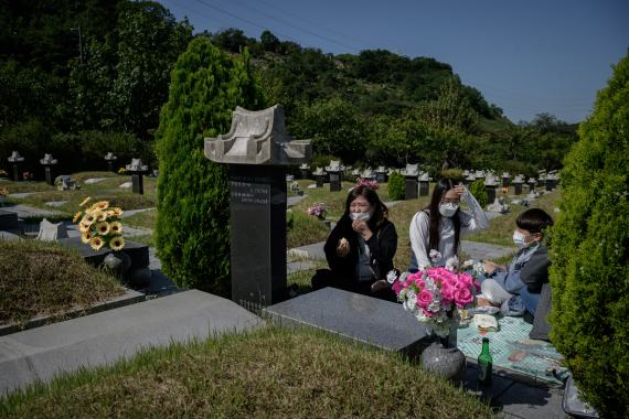 A family sit before a grave after performing a traditional ceremony of remembrance in Incheon where the local government was encouraging people to visit cemeteries ahead of Chuseok to avoid large gatherings [Ed Jones/AFP]