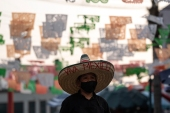 A man wearing a sombrero walks near Santa Cecilia square in downtown Tijuana, on September 15, on the 210th anniversary of Mexico's Independence. [Guillermo Arias/AFP]