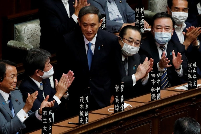 Japanese legislators applaud newly-elected Prime Minister Yoshihide Suga after he won a vote in parliament [Kim Kyung-Hoon/Reuters]