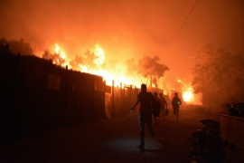 Refugees and migrants run as fires blaze in the Moria refugee camp on the northeastern Aegean island of Lesbos, Greece. [Panagiotis Balaskas/AP Photo]