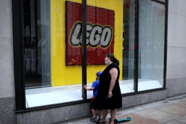 A woman and a child look through the windows of the closed Lego store at Rockefeller Center on 5th Avenue during the outbreak of the coronavirus in Manhattan, New York, US [File: Mike Segar/Reuters]