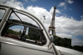 A car of the Paris company 2CVParisTour.com is seen parked in front of the Eiffel Tower in Paris, France [File: Benoit Tessier/Reuters]