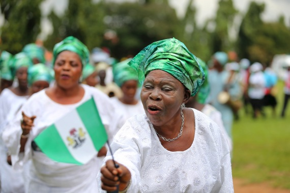 A woman raises the Nigerian flag as she participates in a parade to commemorate Nigeria's 55th Independence Day in this 2015 photo [File: Akintunde Akinleye/Reuters]