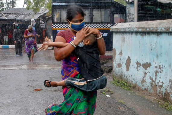 A woman carrying her son as she tries to protect him from heavy rain while they rush to a safer place, following their evacuation from a slum area before Cyclone Amphan made landfall, in Kolkata, India, May 20, 2020 [File: Rupak De Chowdhuri/Reuters]