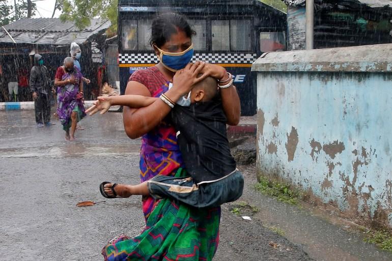 Seorang wanita menggendong putranya saat dia mencoba melindunginya dari hujan deras saat mereka bergegas ke tempat yang lebih aman, menyusul evakuasi mereka dari daerah kumuh sebelum Topan Amphan menghantam, di Kolkata, India, 20 Mei 2020 [File: Rupak De Chowdhuri / Reuters]