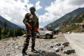 An Indian Central Reserve Police Force (CRPF) personnel stands guard at a checkpoint along a highway leading to Ladakh, at Gagangeer in Kashmir's Ganderbal district [File: Danish Ismail/Reuters]