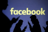 Silhouettes of mobile users are seen next to a screen projection of Facebook logo in this picture illustration taken March 28, 2018 [File:Dado Ruvic/Illustration/Reuters]