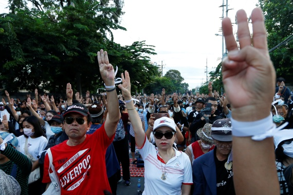Pro-democracy protesters flash the three-fingers salute while attending a mass rally to call for the removal of Prime Minister Prayuth Chan-ocha and reforms in the monarchy in front of parliament in Bangkok [Soe Zeya Tun/Reuters]