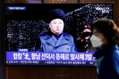 A woman walks past a TV broadcasting file footage for a news report on North Korea firing an unidentified projectile, in Seoul, South Korea, March 9, 2020 [File: Heo Ran/ Reuters]