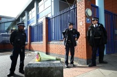 Flowers are laid outside the custody centre where a British police officer has been shot dead in Croydon, south London [Hannah McKay/Reuters]