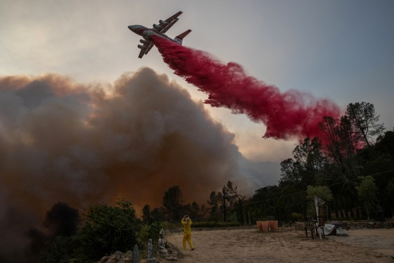 A plane drops red fire retardant on the Glass Fire at a vineyard in Deer Park. [Adrees Latif/Reuters]