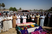 Mourners pray near coffins containing the bodies of victims killed in rocket attacks on Monday in Abu Ghraib district on the outskirts of Baghdad [Saba Kareem/Reuters]