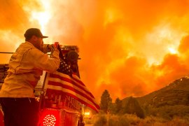 A firefighter fixes a United States flag hanging on a fire truck in the Lake Hughes fire in Angeles National Forest on August 12, 2020, north of Santa Clarita, California [File: Ringo H.W. Chiu/AP Photo]