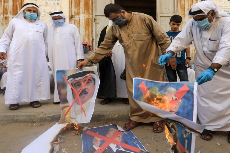 Palestinians burn images of the Bahraini king, US president and the Israeli prime minister during a protest in Deir al-Balah in central Gaza Strip on Saturday [Mahmud Hams/AFP]