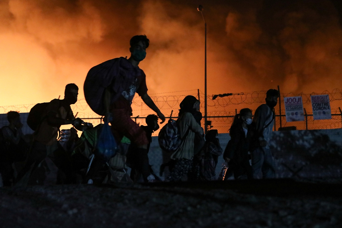 Refugees carry their belongings as they flee the devastating blaze. [Elias Marcou/Reuters]