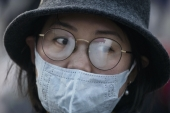 A woman's glasses fog up while wearing a protective mask at Beijing Station in China [File: Kevin Frayer/Getty Images]