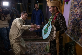 Kashmiri groom Haseeb Mushtaq is greeted with an offer of some hand sanitiser as he arrives at his bride's home on the outskirts of Srinagar for their wedding ceremony. [Dar Yasin/AP Photo]