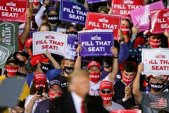 Supporters of President Donald Trump hold up signs as he speaks at a campaign rally in Swanton, Ohio [Tony Dejak/The Associated Press]