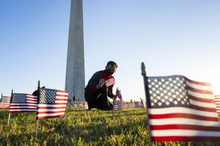 Supporters of the COVID Memorial Project place US flags on the National Mall. The US coronavirus death toll has surpassed 450,000 [File: Jim Lo Scalzo/EPA-EFE]