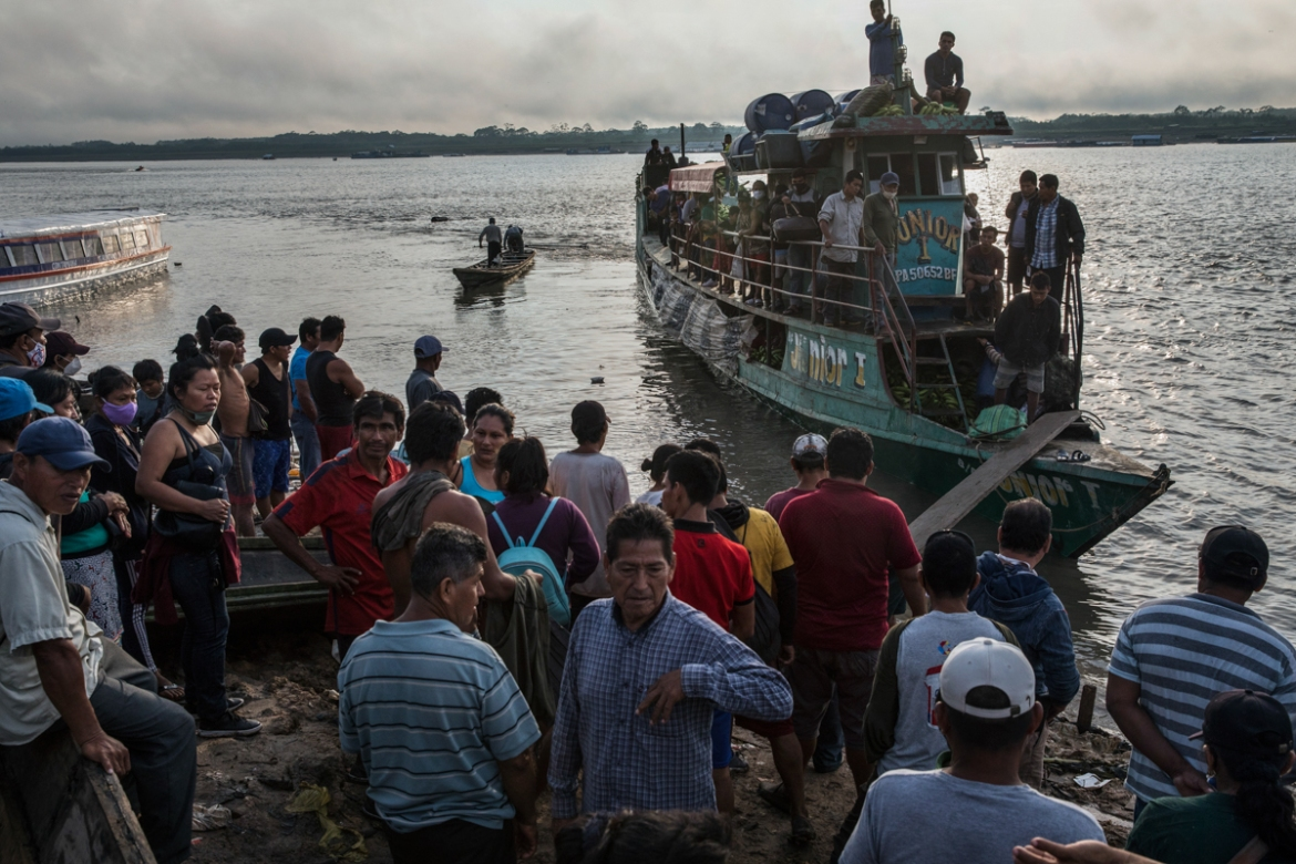 Passengers arrive in a public taxi boat to the Shipibo Indigenous community of Pucallpa, located along the Ucayali river in the Amazonian rainforest of eastern Peru. Transportation is one of the biggest hurdles in treating Indigenous groups - some can only be reached by helicopter or an eight-hour boat ride. [Rodrigo Abd/AP Photo]