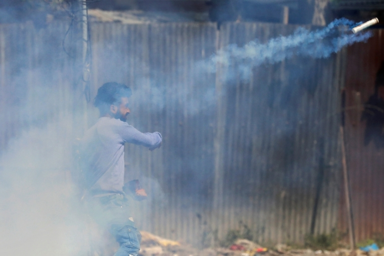 A Kashmiri demonstrator throws a tear gas canister fired by the police during a protest in Srinagar [Danish Ismail/Reuters]