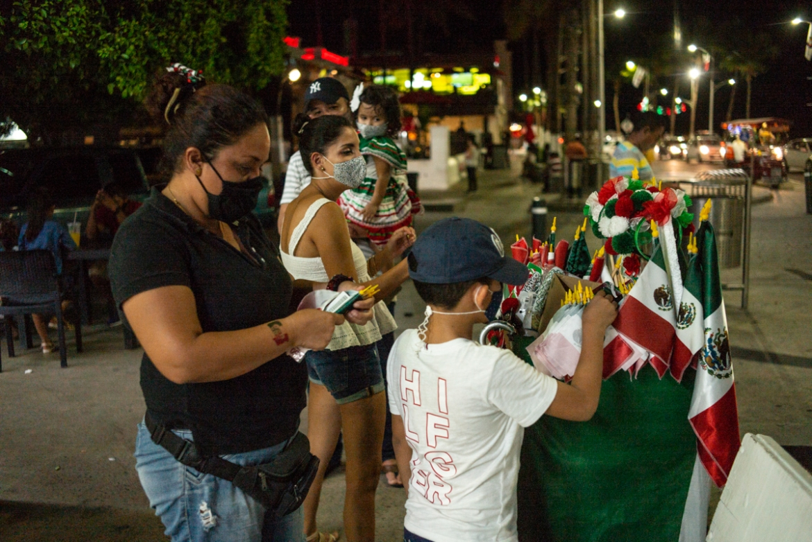 A child looks for Mexican flags at a stand on the Malecon de la Paz as part of the Independence Day celebrations on September 15 in La Paz. [Alfredo Martinez/Getty Images]