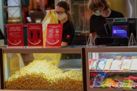 Concessions stand workers stock the bins with popcorn and other treats as the theatre opens for some of the first showings at the AMC theatre in West Homestead, Pennsylvania [AP Photo/Keith Srakocic]