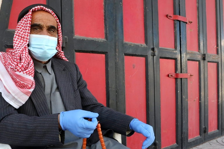 An elderly Palestinian sits with mask and latex gloves outside a closed shop in the centre of Hebron in the occupied West Bank [File: Hazem Bader/AFP]