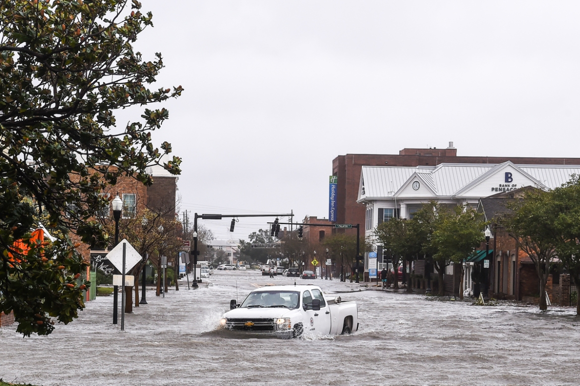 A city worker drives through the flooded streets in downtown Pensacola. [Chandan Khanna/AFP]