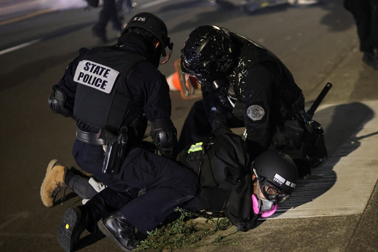 Police detain a demonstrator on the 100th consecutive night of protests against police violence and racial inequality in the US state of Portland [Carlos Barria/Reuters]