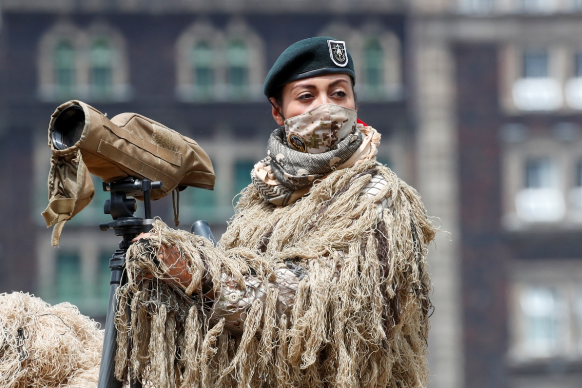 A soldier wears camouflage and a face mask during a military parade in Mexico City's Zocalo square. [Carlos Jasso/Reuters]