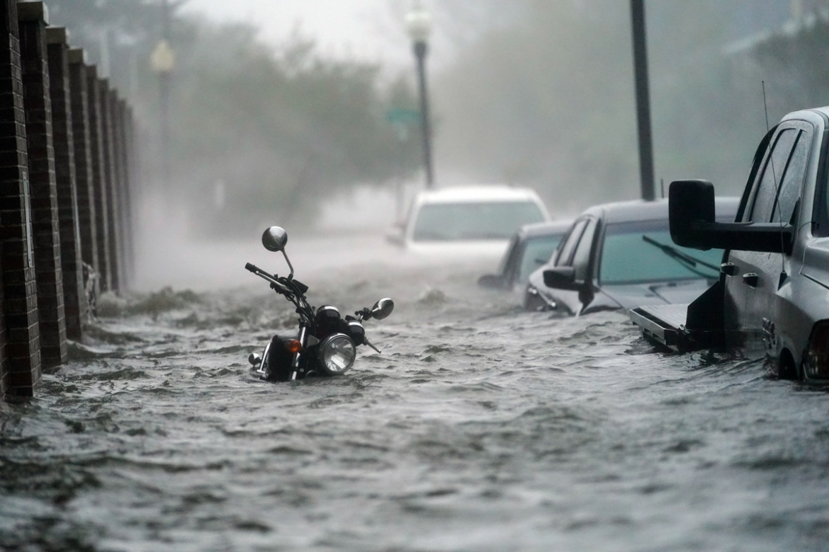 Cars and a motorcycle are underwater as water floods streets in Pensacola. Some parts of the coast were inundated with more than 600mm of rainfall, as the slow-moving storm flooded communities. [Gerald Herbert/AP Photo]