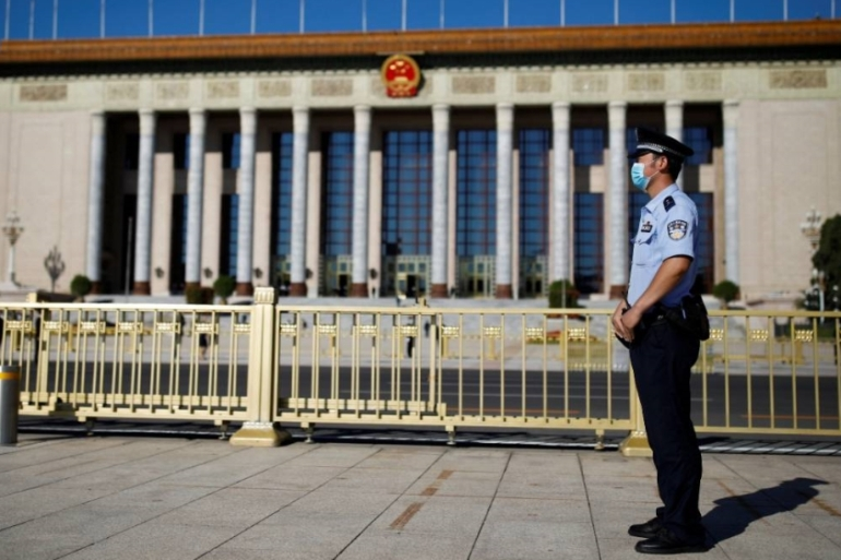 Reports said seven officers simultaneously visited the residence of both journalists just after midnight on Thursday and told the reporters of the ban on them leaving China [Carlos Garcia Rawlins/Reuters]