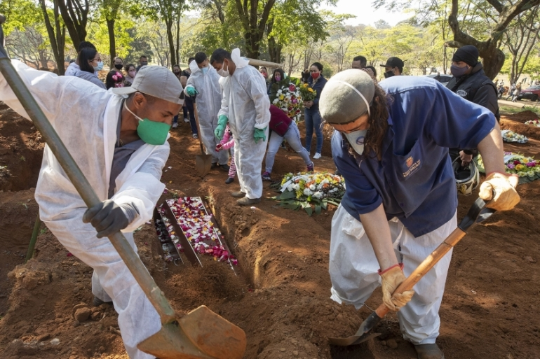 Cemetery workers bury 65-year-old Maria Joana Nascimento, whose family members, in the background, suspect she died of COVID-19, on August 6 at Vila Formosa cemetery in Sao Paulo, Brazil, which is nearing three million cases of COVID-19 and 100,000 deaths (AP Photo/Andre Penner) [The Associated Press]