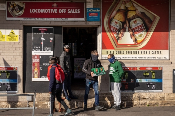A customer wearing a protective face scarf leaves a liquor store carrying a crate of beer in Cape Town, South Africa, which in late March implemented one of the world's strictest lockdowns to curb the spread of COVID-19 [File: Dwayne Senior/Bloomberg]