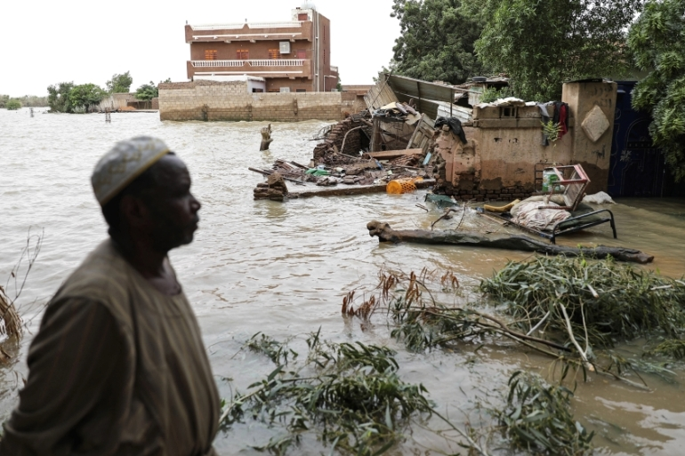 A man walks beside a flooded road in the town of Shaqilab, about 24km (15 miles) southwest of the capital, Khartoum, Sudan, on August 31, 2020 [AP Photo/Marwan Ali]