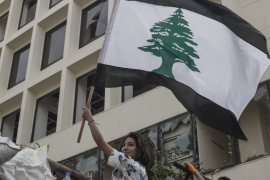 An anti-government protester holds a Lebanese flag which has had the usual red stripes replaced with black as a sign of mourning, during a demonstration on September 1, 2020 in Beirut, Lebanon [Sam Tarling/Getty Images]