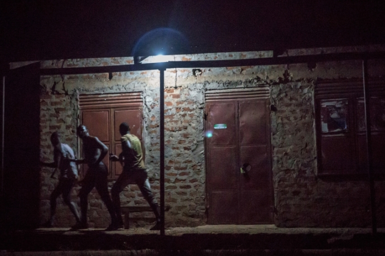Men run to avoid security forces patrolling the streets looking for people violating the coronavirus curfew in Gulu, Uganda on 10 April, 2020. [Sally Hayden/LightRocket via Getty Images]