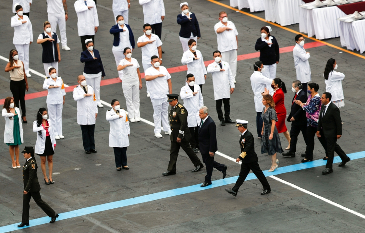 Doctors and nurses from different public health institutions who have fought against COVID-19 receive recognition from Mexican President Andres Manuel Lopez Obrador during the military parade for the 210th anniversary of Independence Day. [Henry Romero/Reuters]