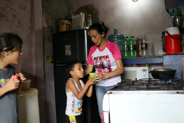 Nurse Flor Perez hands a cup of water to her son at their house in a low-income neighbourhood in Caracas, amid the outbreak of the coronavirus in Venezuela [File: Manaure Quintero/Reuters]