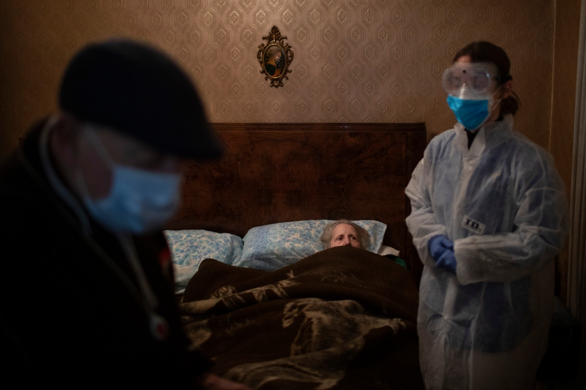Josefa Ribas, 86, who is bedridden, looks at nurse Alba Rodriguez as Ribas' husband, Jose Marcos, 89, stands by in their home in Barcelona, Spain, on March 30, 2020. Ribas suffers from dementia, and Marcos fears for them both if the virus enters their home. 'If I get the virus, who will take care of my wife?' [Emilio Morenatti/AP Photo]