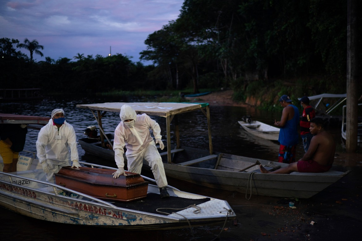 SOS Funeral workers transport by boat the coffin of an 86-year-old woman who lived by the Negro River and who is suspected to have died of COVID-19, near Manaus, Brazil, on Thursday, May 14, 2020. [Felipe Dana/AP Photo]