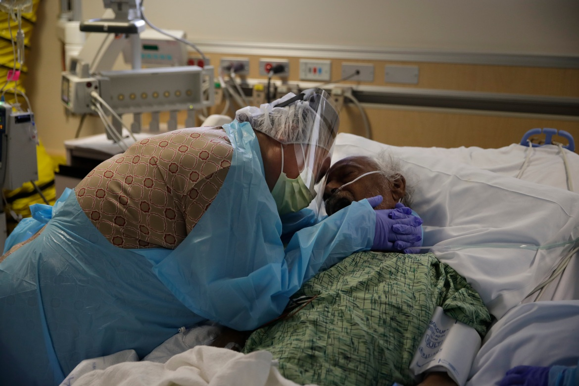 Romelia Navarro, 64, weeps while hugging her husband, Antonio, in his final moments in a COVID-19 unit at St Jude Medical Center in Fullerton, California, on Friday, July 31, 2020. [Jae C Hong/AP Photo]