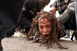 Louisville police detain a man after a group marched in Louisville, Kentucky. [John Minchillo/AP Photo]