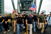 Members of the Proud Boys and other right-wing demonstrators march across the Hawthorne Bridge in Portland, Oregon during a rally in August 2019 [File: Noah Berger/AP]